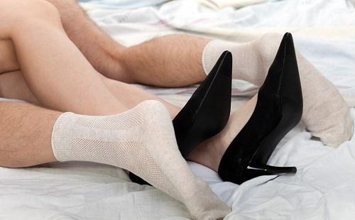 мужчина и женщина занимаются сексом на кровати видны только ноги в носках и туфлях на каблуках