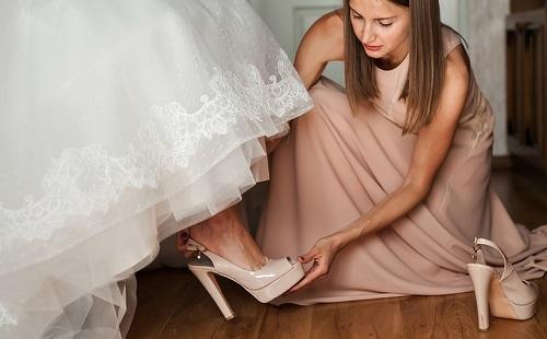 дружка помогает обуть туфли невесте