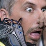 мужчина с бородой в ужасе нюхает вонючие кроссовки